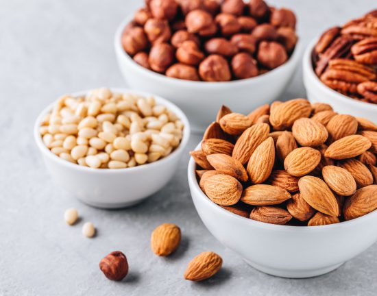 Almonds, pecans, pine nuts and hazelnuts in white bowls on grey background. Nuts mix. Healthy food and snack.