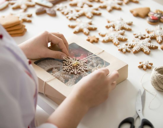 Close up of female confectioner hands. Christmas wrapping ideas, tutorial to make plain brown wrapping paper look festive. Christmas concept photo, lifestyle